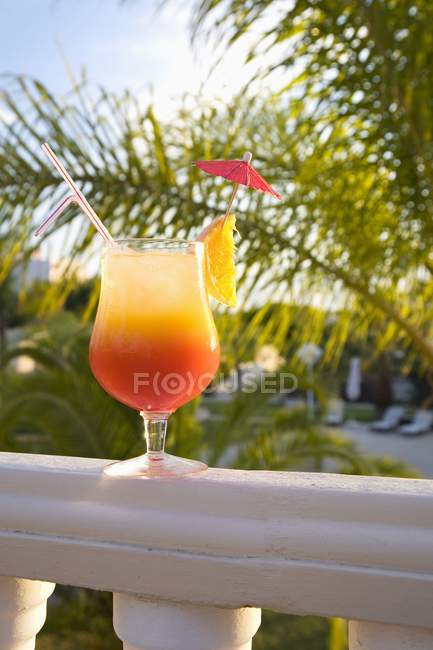Daytime view of cocktail with orange slice, straw and umbrella on balcony railing — Stock Photo