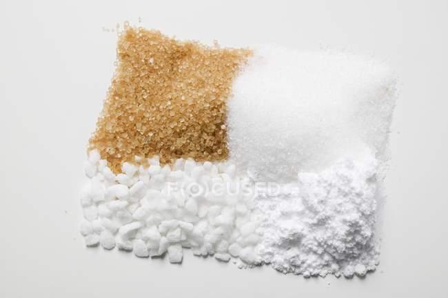 Крупным планом зрения четырех различных видов сахара в кучах — стоковое фото