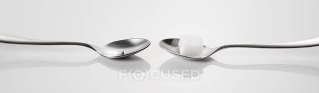 Closeup exibição de duas colheres com cubo de açúcar e adoçante — Fotografia de Stock