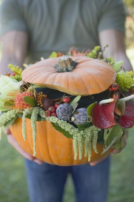 Женщина, держащая тыквы, украшенная цветами — стоковое фото
