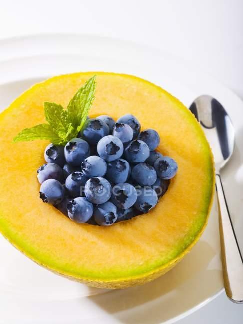 Fresh blueberries in cantaloupe half — Stock Photo