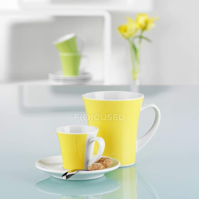 Closeup view of yellow cups in with cookies on white reflective surface — Stock Photo