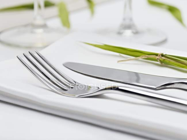 Closeup view of knife and fork on fabric napkin — Stock Photo