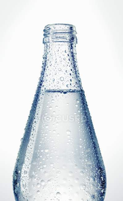 Closeup view of wet glass bottle of water — Stock Photo