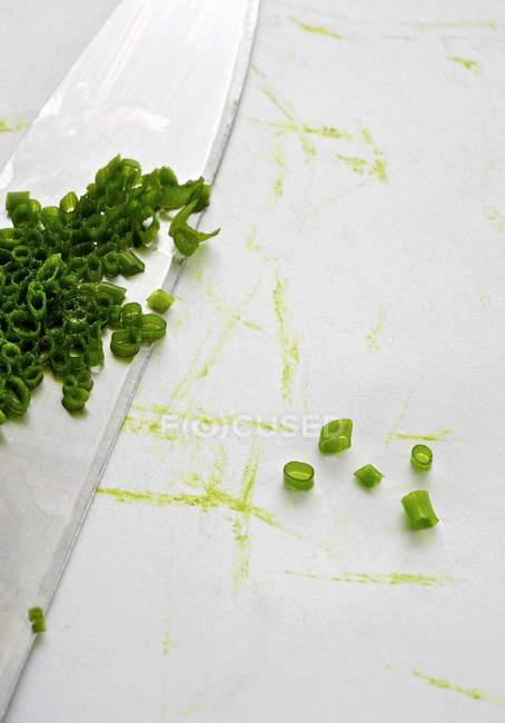 Fresh chopped chives with knife — Stock Photo