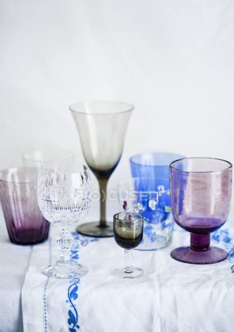 Elevated view of various drinking glasses on white tablecloth — Stock Photo