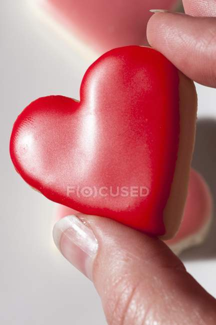 Hand holding heart-shaped biscuit — Stock Photo