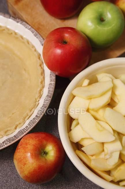 Vista de cerca de manzanas enteras y cortadas en rodajas con corteza de pastel - foto de stock