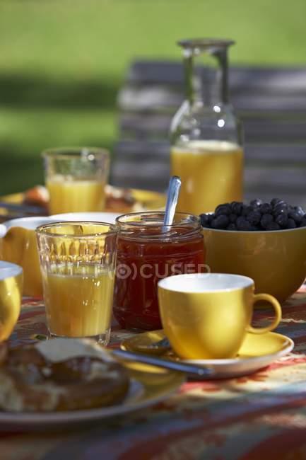 Frühstück mit Orangensaft, Gebäck und Marmelade — Stockfoto