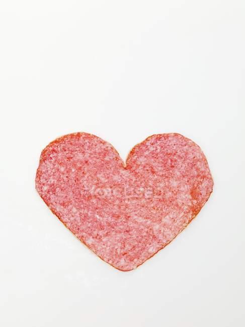 Salami cut in heart shape — Stock Photo