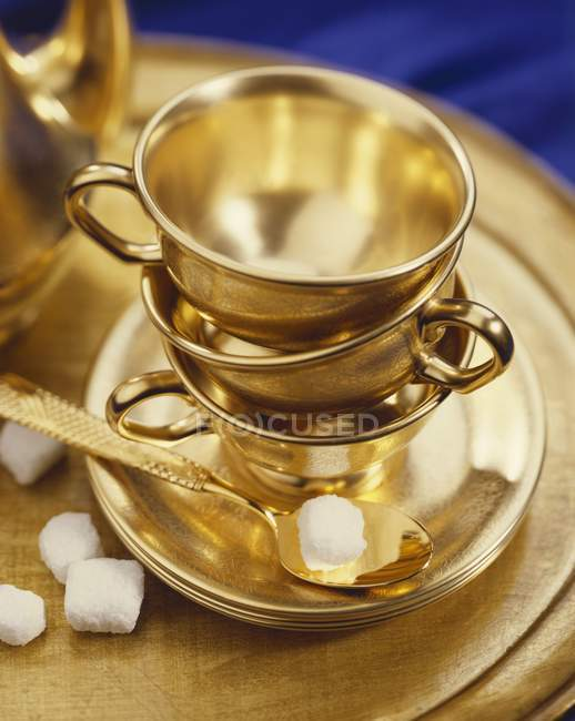Closeup view of golden tea cups, saucers and spoon with sugar cubes — Stock Photo