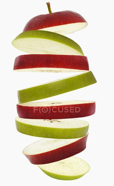 Flying slices of red and green apples — Stock Photo
