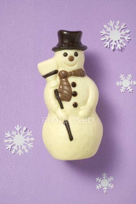 Крупным планом вид шоколада снеговика, окруженный бумаги снежинки — стоковое фото