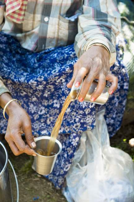 Closeup view of woman pouring tea from cup to cup — Stock Photo
