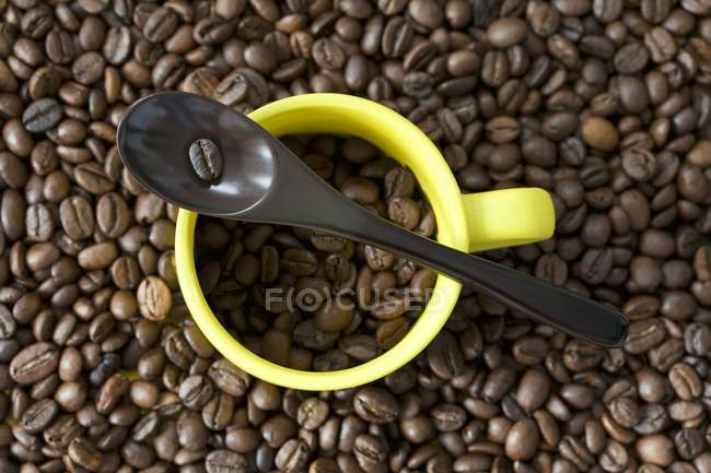Espresso cup and spoon on coffee beans — Stock Photo