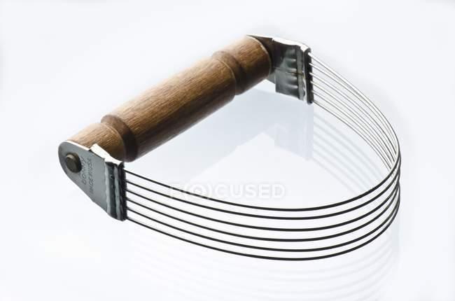 Крупним планом вигляд металевих тісто катер з дерев'яною ручкою на білій поверхні — стокове фото