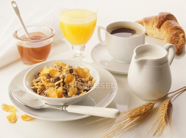 Desayuno de muesli, zumo de naranja y croissant - foto de stock