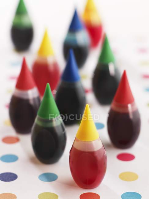 Closeup view of food coloring bottles on dotted surface — Stock Photo