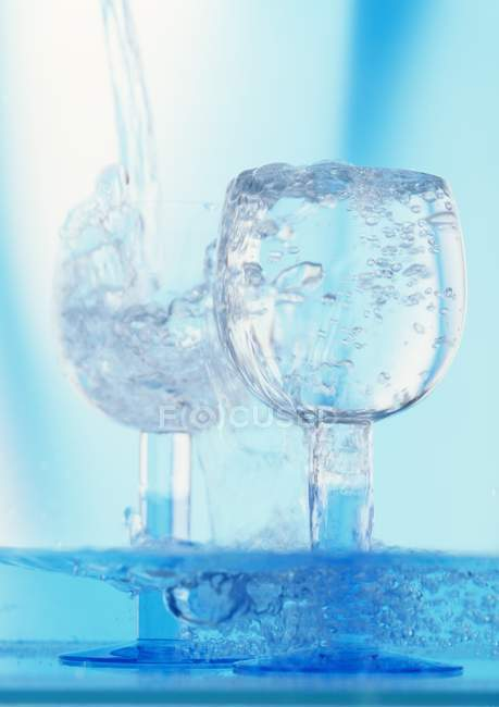 Pouring water into glasses — Stock Photo