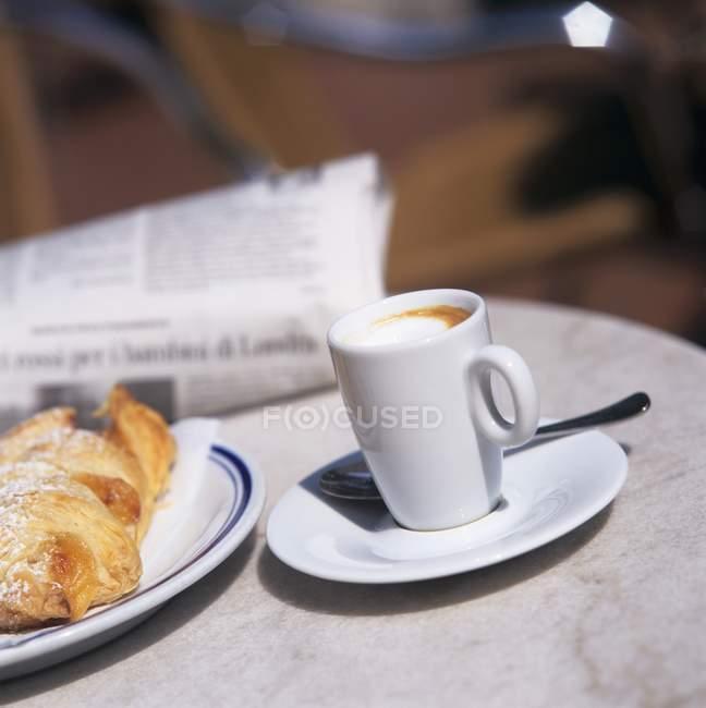 Маккиато с булочками и газетой — стоковое фото