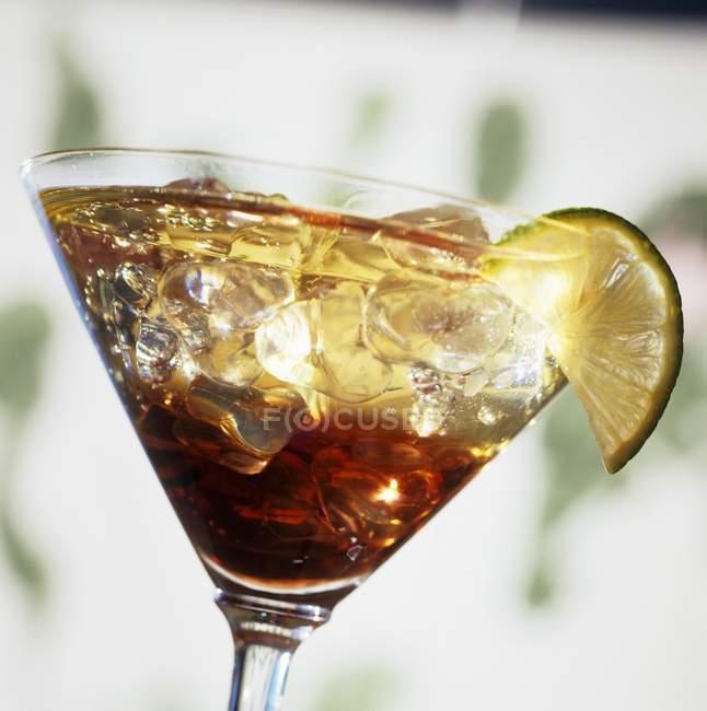 Vista del primo piano di Kir cocktail con cubetti di ghiaccio e fetta di lime in vetro — Foto stock