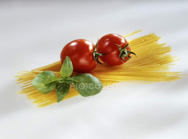 Bundle of raw Spaghetti with tomatoes — Stock Photo