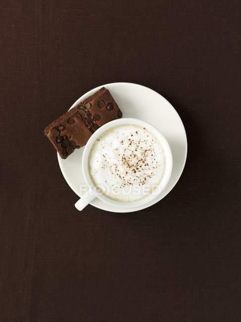 Tazza di caffè con latte e biscotto che serve — Foto stock