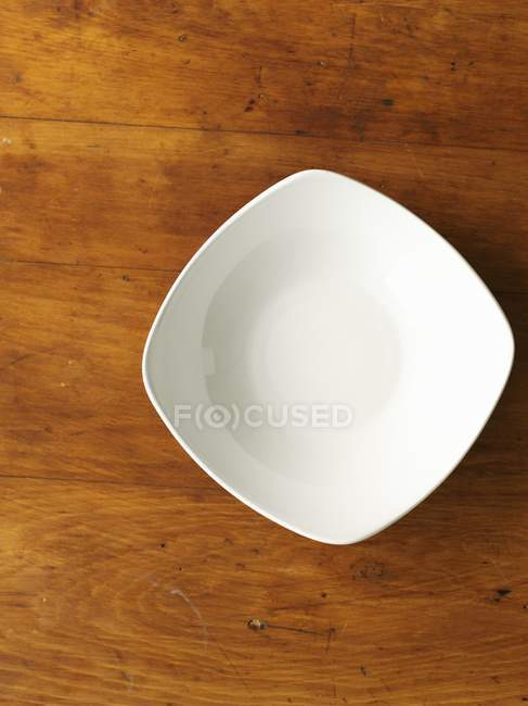 Top view of a white porcelain bowl on a wooden surface — Stock Photo