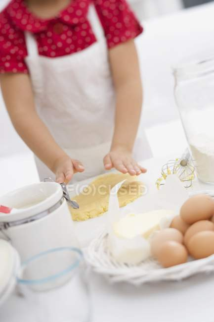 Tilted view of girl flattening dough with hands — Stock Photo