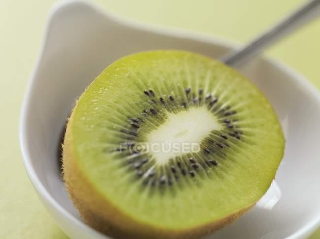 Kiwi dans un bol avec une cuillère — Photo de stock