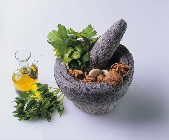 Mortar and pestle with ingredients for parsley Pesto — Stock Photo