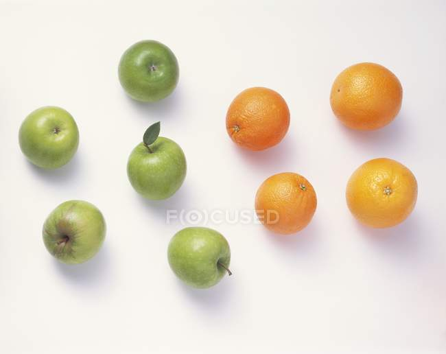 Green apples and oranges — Stock Photo