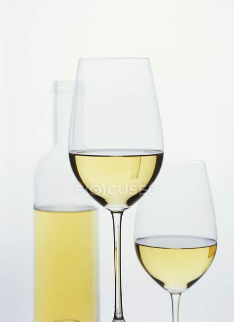 Copos de vinho branco na frente da garrafa — Fotografia de Stock