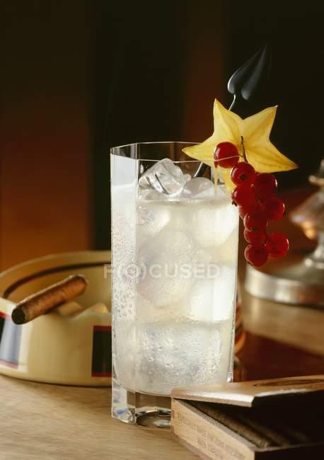 Vista da vicino del cocktail con ghiaccio, fetta di starfruit, ribes rosso e sigaro sul posacenere — Foto stock
