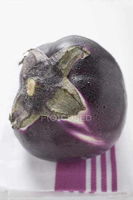 Round aubergine with drops of water — Stock Photo