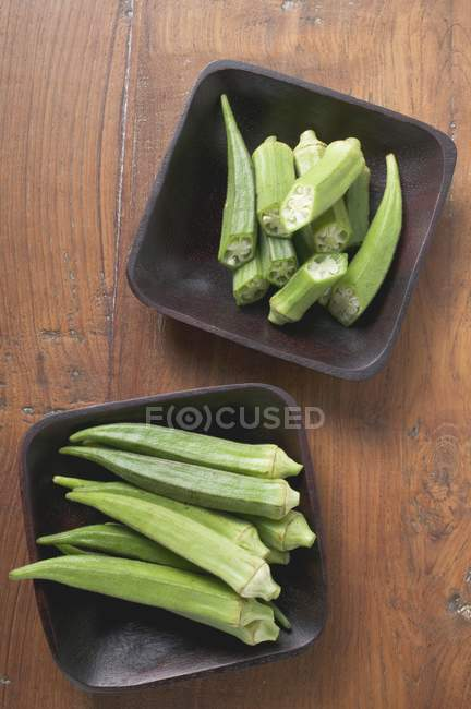 Whole and halved okra pods — Stock Photo