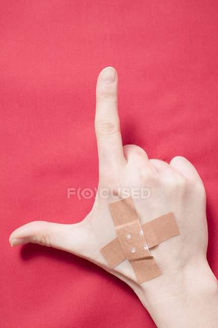 Main avec croisés plâtres de friction sur la surface rouge montrant pouce et pointer du doigt — Photo de stock