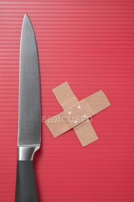 Coltello e intonaci incrociati su superficie a strisce rosse — Foto stock