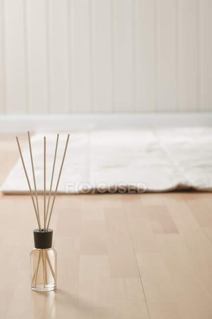 Bâtonnets d'encens aromatiques et tapis sur parquet — Photo de stock