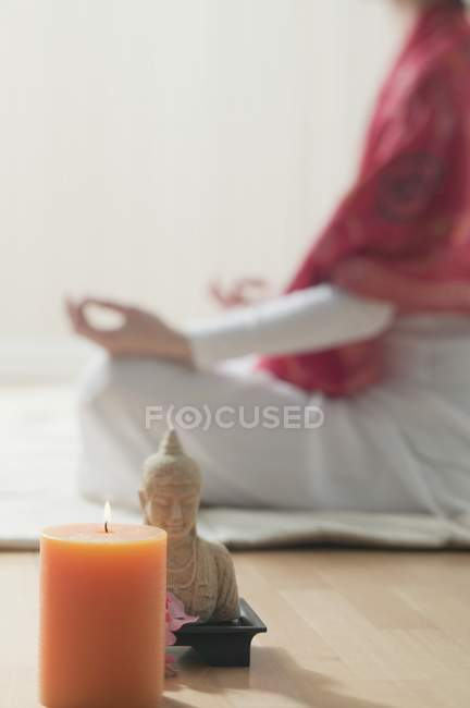 Candle and Buddha statue with woman sitting cross-legged on background — Stock Photo