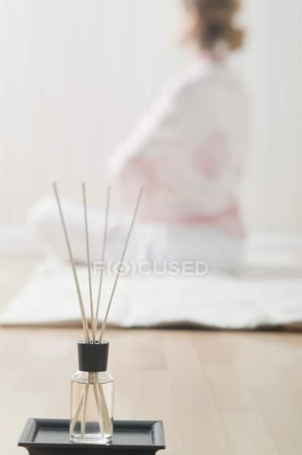 Bâtonnets d'encens à l'huile parfumée et femme assise sur le fond — Photo de stock