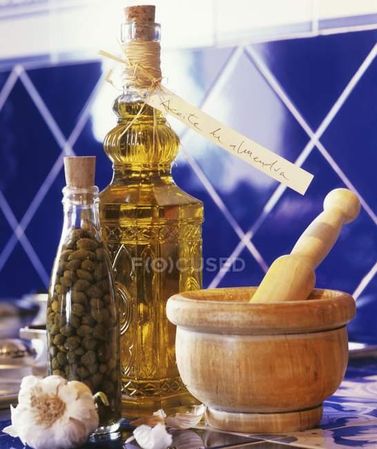 Крупним планом з видом на часнику пляшка каперси, пляшка Мигдальне масло, дерев'яні Ступка — стокове фото