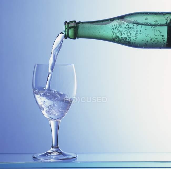 Einschenken von Mineralwasser — Stockfoto
