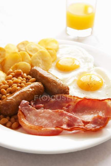 English breakfast with orange juice on white plate with eggs, meat and beans — Stock Photo