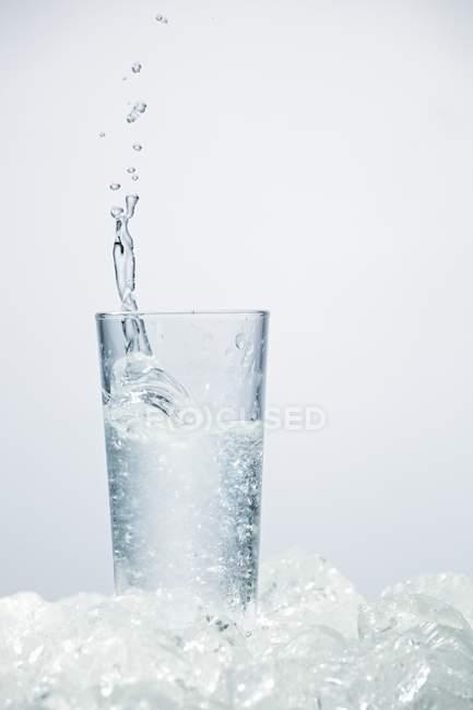 Крупным планом вид льда плескались в стакан УЗО — стоковое фото