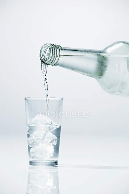 Заливки Горілка на скло, що містить кубики льоду — стокове фото