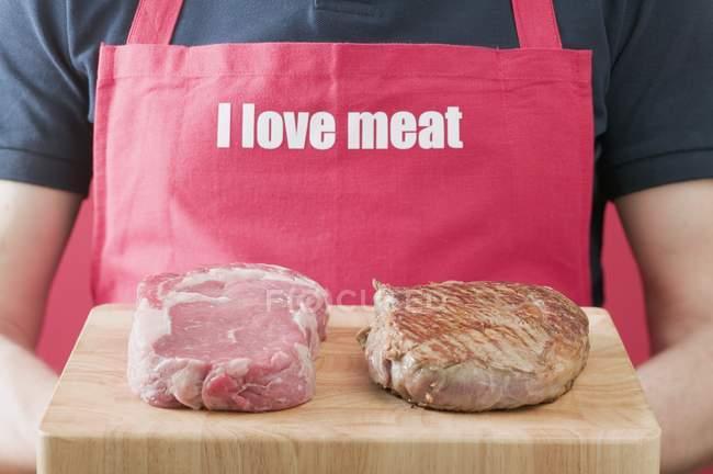 Homme tenant des steaks — Photo de stock