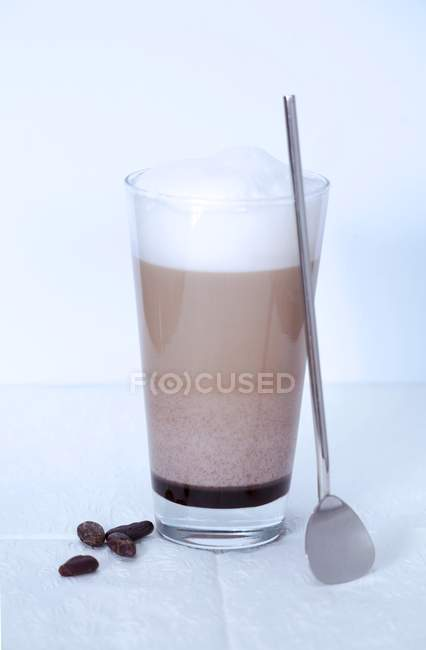Closeup view of Caffe mocha with foamed milk, spoon and beans — Stock Photo