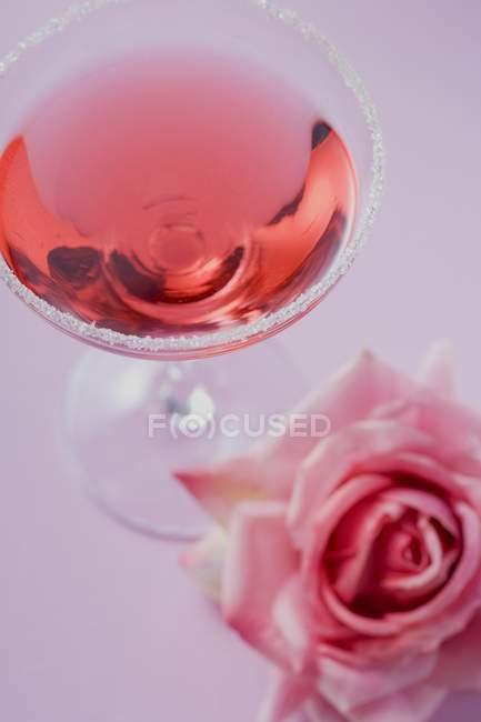 Nahaufnahme von Rosenlikör im Glas mit Zuckerrand und Rose daneben — Stockfoto