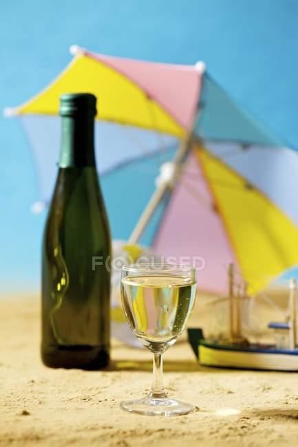 Primo piano vista di vetro e bottiglia di vino bianco sulla spiaggia di sabbia — Foto stock